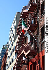 Old brick building with Irish flag on fire escape