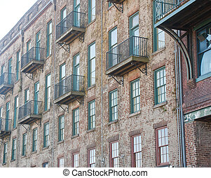 Old Brick Building with Red and Green Windows and Balconies