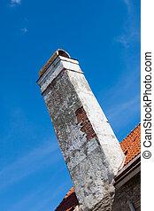 old brick chimney on orange tile roof