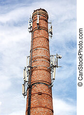 Old brick chimney with antennas of cellular communication