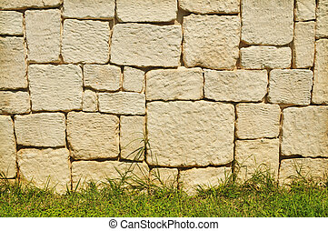 Old brick stone wall background with grass