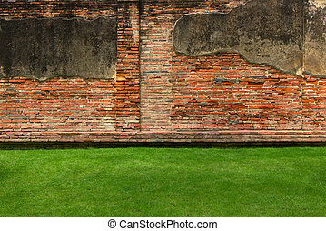 Old brick wall background with green grass