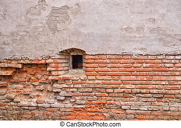 Old brick wall from a ancient fortress with small window