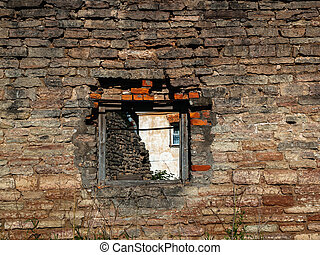 Old brick wall of a ruined building with a window