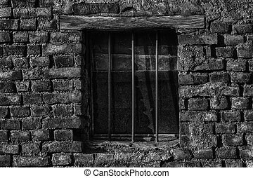 Old brick wall with brick filled window with grid.