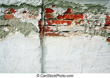 Old brick wall with broken plaster