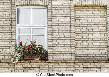 Old brick wall with window and flowers