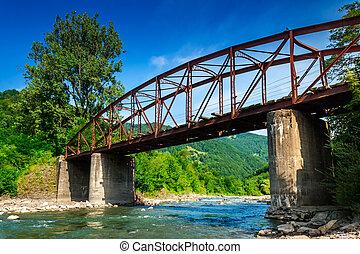 old bridge - old iron bridge over mountain river