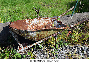 old broken and rusty wheelbarrow abandoned on a lawn