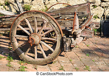 Old broken-down wooden cart with rusty wheels