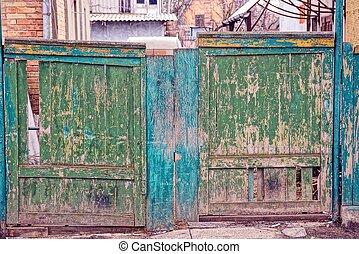 old broken green wooden gate in the street