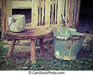 old broken tin bucket and an aluminum pot over the stool