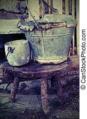 old broken tin bucket and an aluminum pot over the stool of the