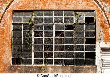 Old broken window glass on orange brick wall