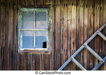 Old broken window in the wooden wall of the house and old wooden ladder