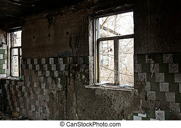 old broken windows in the charred dirty room of an abandoned house