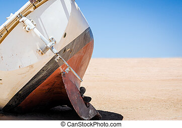 old broken yacht lay on the sand in the desert in Egypt
