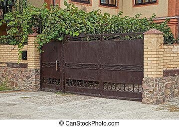 old brown iron gate and a brick fence in green vegetation on the street