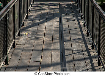 Old brown rustic Wooden walkway with sunlight shine passed through trees and make shadow on the floor.