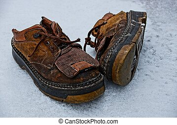 old brown shoes on white snow