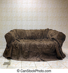 Old brown textile couch in bathroom