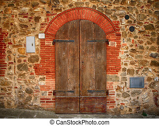 Old brown wooden door in ancient house, Tuscany, Italy.