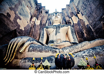 Old buddha statue on wall in ancient temple thailand Sukhothai historical park