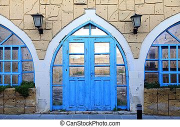 Old building facade with blue door and window, Larnaca, Cyprus