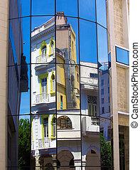 Old building mirrored in modern house window, Havana