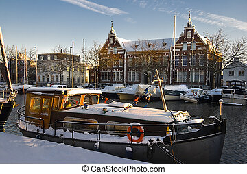 Old buildings and old ship with snow on sunny winterday