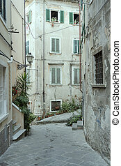 old buildings on narrow street in town historical center, Carrara, Italy