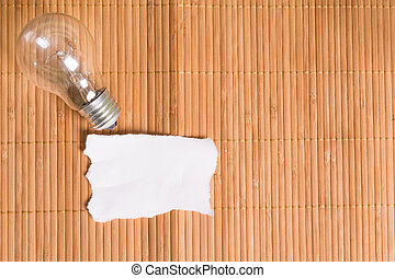 Old bulb and blank piece of paper on a wooden background
