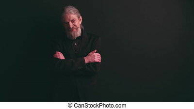 Old business man in tux standing with arms crossed in a studio on black background, looking to the camera, shares, stock, money. Camera close up. Prores 422.