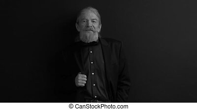 Old business man with long beard in dark business clothes with one hand in chest pocket looking at camera in semi-lit room on black background. Black and white portrait. Waist portrait. Prores 422.