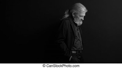Old business man with long hair and beard in dark business clothes standing sideways in semi-lit room on black background. Black and white portrait. Waist portrait. Prores 422.