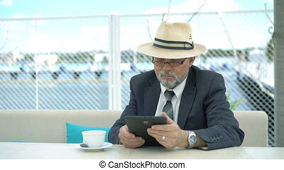 Old businessman using tablet and looking on wristwatch at the table. 4K