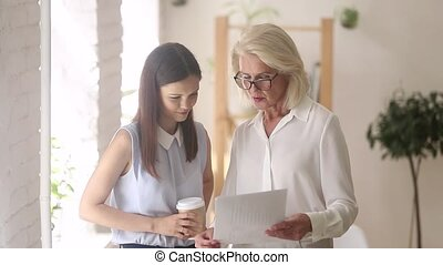 Old businesswoman consulting young client about contract make deal handshaking