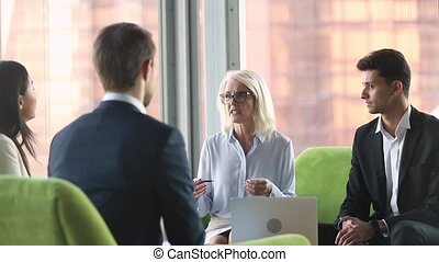 Old businesswoman talking to diverse partners at...
