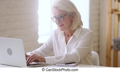 Old businesswoman working with laptop and papers sitting at...