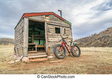 old cabin and fat bike - old cabin in Rocky Mountains and a ...