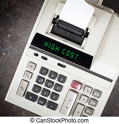 Old calculator showing a text on display - high cost