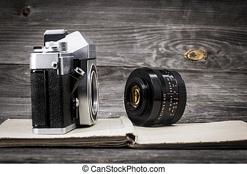 old camera at vintage book, wooden background