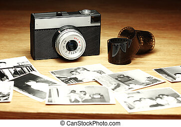 Old camera next to film and out of focus black and white photographs