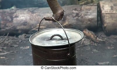 Old camp pot hanging over the fire. Tourist pot hanging on a...
