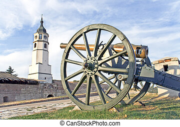 Old cannons on fortress and tower over blue sky