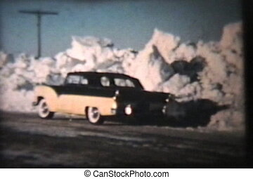 A black and yellow vintage 57 Ford is parked in front of massive snow banks after a winter blizzard in the prairies. (Scan from archival 8mm film)