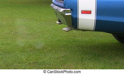 Old car polluting air closeup
