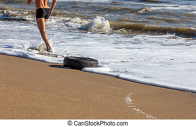 Old car tires on the beach, Water and sea coast pollution car tires on sand beach, An image of an old car tire ingrown into the sand. Old car tires with seaweed stuck on.