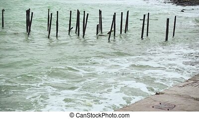 Old carcass from the pier to the sea - Old metal carcass of...