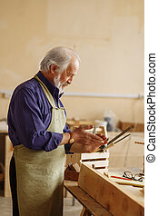 old carpenter is rubbing his hands together after finishing work